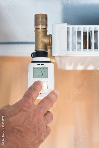 Photo  Person's Hand Adjusting Temperature On Thermostat