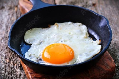 Foto op Plexiglas Gebakken Eieren Breakfast the fried egg in a iron frying pan