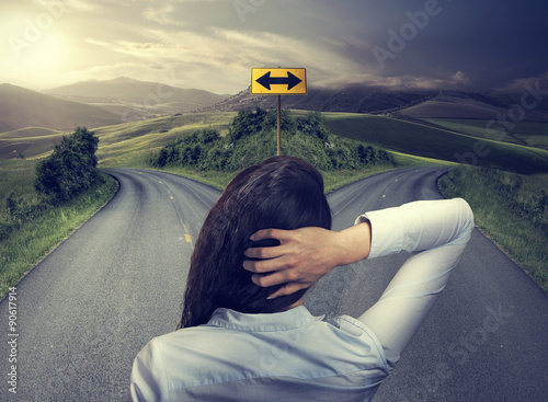 Fotografie, Tablou  business woman in front of two roads thinking deciding