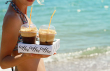 Attractive Female Waiters Holding Two Ice Frappe Coffee On The Beach Near Sea. Young Woman Enjoyng During Summer Holiday, Vacation  On Tropical Resort By Ocean. Sunset Colors.