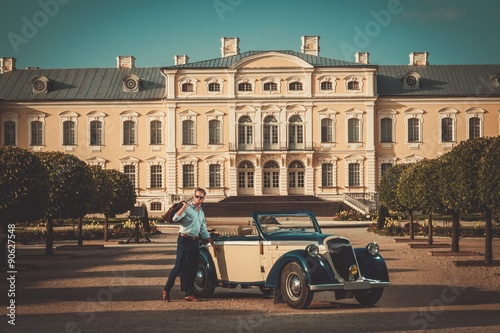 Fotografie, Obraz  Confident wealthy young man with briefcase near classic convertible