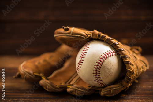 Fotografija  Leather baseball glove and ball on a wooden bench