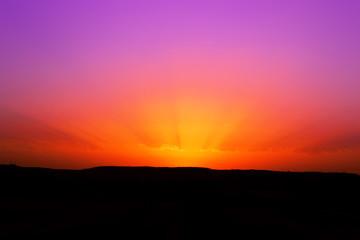 Raggi di sole in una foto di un tramonto rosso e viola