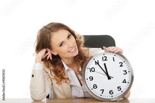 Fotografia, Obraz  Businesswoman with clock by a desk.