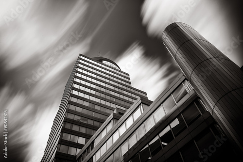Long time exposure of clouds over modern office building. Black and white picture.