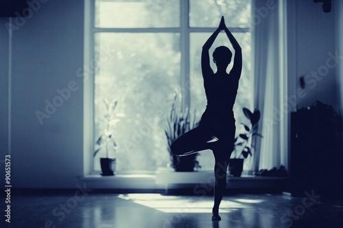 Fotografia  fitness girl yoga silhouette in the room