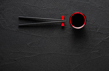 FototapetaChopsticks and bowl with soy sauce on black stone background