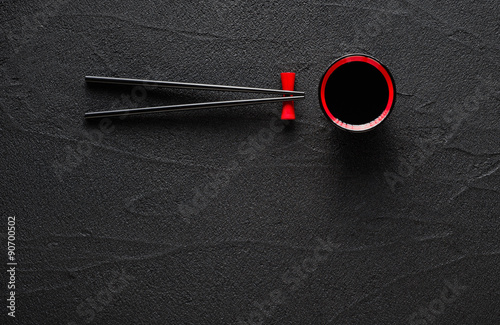 Foto  Chopsticks and bowl with soy sauce on black stone background