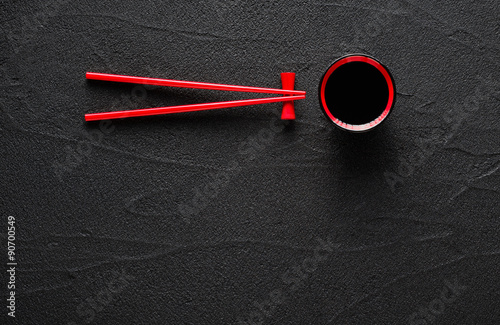 Chopsticks and bowl with soy sauce on black stone background Canvas