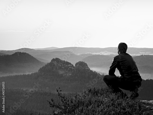 Poster Gris Tall hiker in black in squatting position on a rock in heather bushes, enjoy the scenery