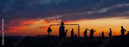 Chicos jugando el fútbol al atardecer en la playa