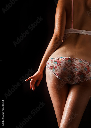 Tela  Rear view of a sexy woman in lingerie over black background.