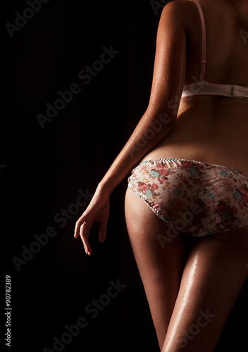Tela  Rear view of a sexy wet woman in lingerie over black background.