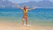 blonde girl in bikini runs out of water shakes wet long hair