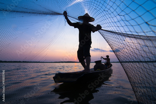 Poster Peche Silhouette of a fisherman throwing his net with sunset.
