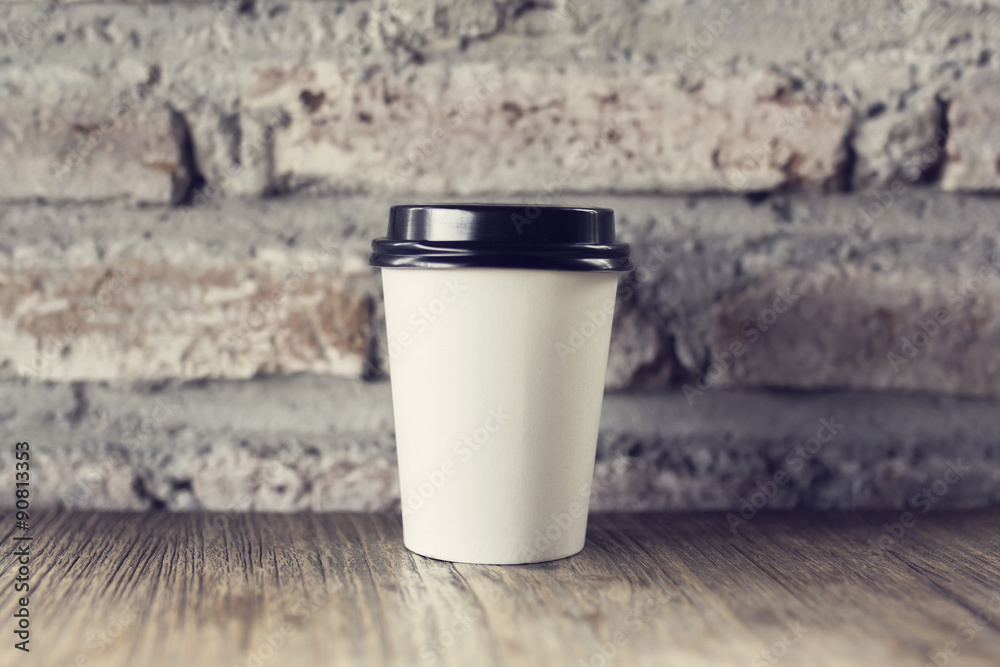 Coffee to go on a wooden table with vintage style wall