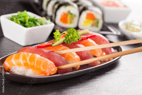 Photo  sushi pieces with chopsticks