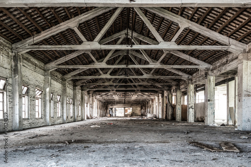 In de dag Industrial geb. Empty industrial loft in an architectural background with bare cement walls, floors and pillars supporting a mezzanine
