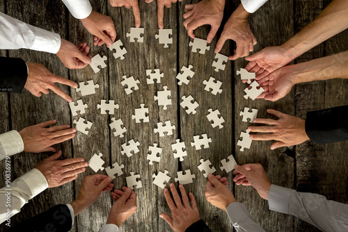 Businessmen Hands Holding Puzzle Pieces on Table Poster