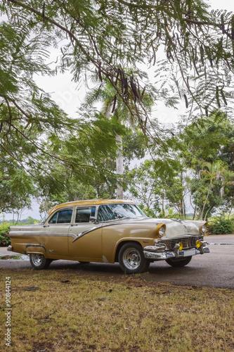 In de dag Havana stary amerykański samochód wśród drzew - Kuba