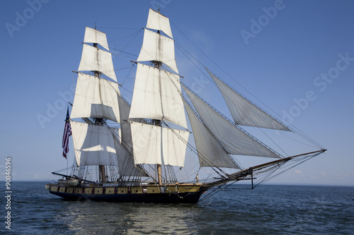 Photo Stands Ship Tall ship with American flag sailing on blue waters