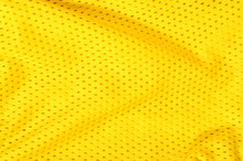 Yellow Textile Pattern As A Background. Close Up On Yellow Crumpled Material With Holes Texture On Fabric.