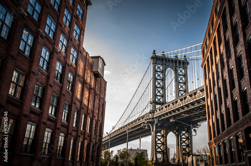 Foto op Aluminium Brug Manhattan bridge seen from a narrow alley enclosed by two brick buildings on a sunny day in summer