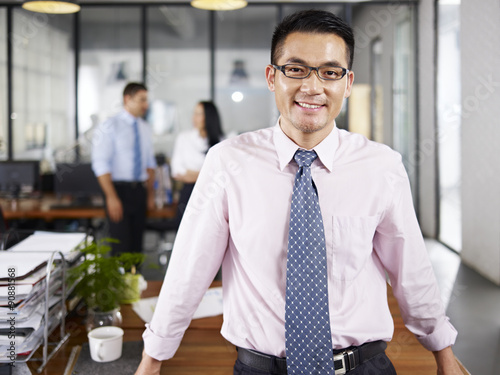 Fotografia asian businessman standing in office arms crossed with multinati