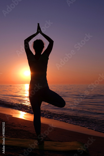 Fototapeta Young healthy woman practicing yoga on the beach at sunset obraz na płótnie
