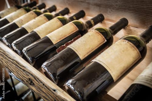 Poster de jardin Bar Old wine bottles on the wine shelf.