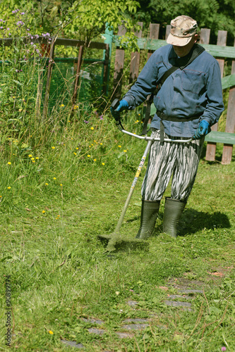 Papiers peints Jardin man mows the grass trimmer