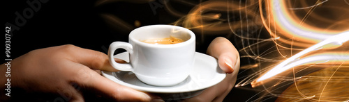 Hands holding cup of coffee on energy lighting background