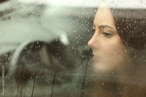 Cuadros en Lienzo Mujer triste mirando a través de una ventana de coche