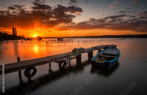 Keuken foto achterwand Grijs Lonely boat at sunset. Magnificent long exposure lake sunset near Varna, Bulgaria
