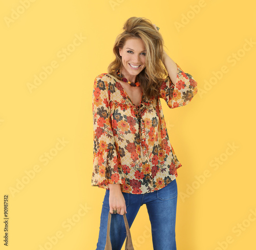 Beautiful trendy woman, isolated on yellow background Wall mural