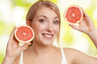 lachende Frau hält 2 halbe Grapefruit