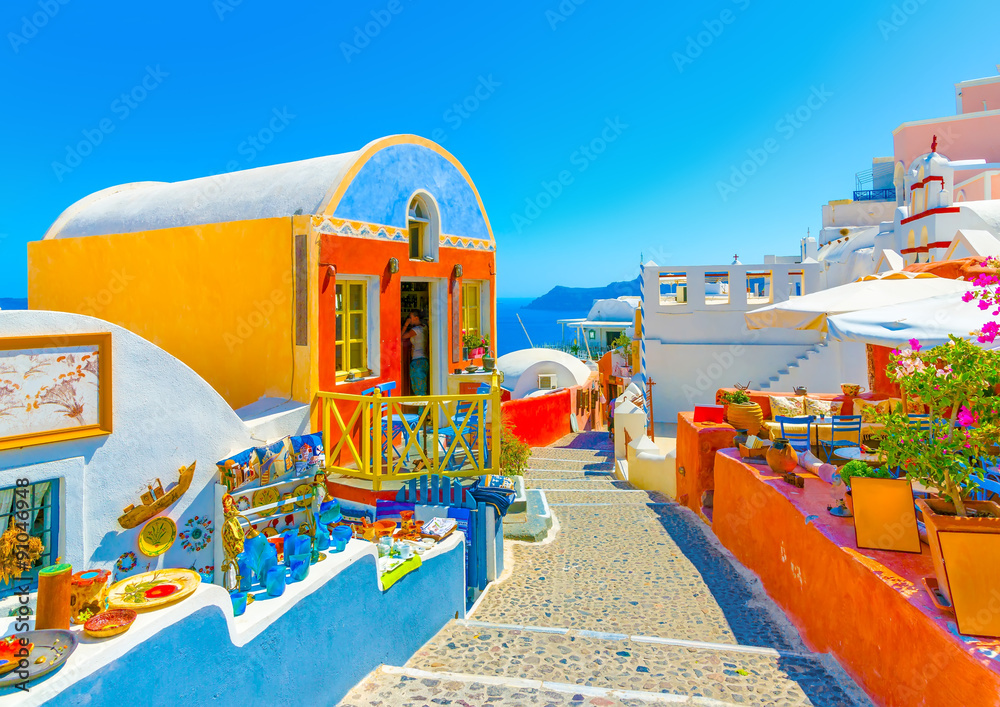 Fototapety, obrazy: Typical colorful narrow street in Oia the most beautiful village of Santorini island in Greece