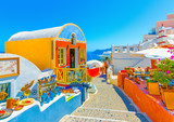 Fototapeta Uliczki - Typical colorful narrow street in Oia the most beautiful village of Santorini island in Greece