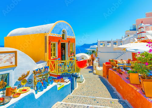 Fototapeta Typical colorful narrow street in Oia the most beautiful village of Santorini island in Greece obraz