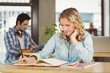 Businesswoman writing in book while working at bright office