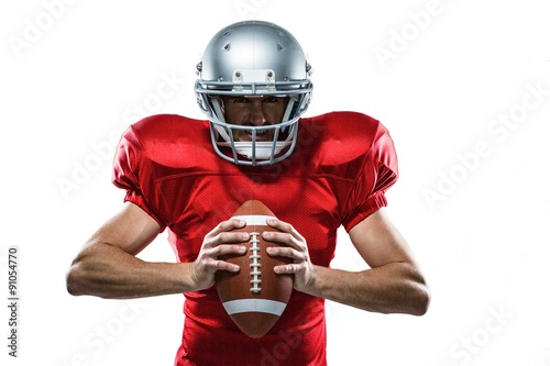 Fotografie, Tablou  American football player in red jersey and helmet holding ball
