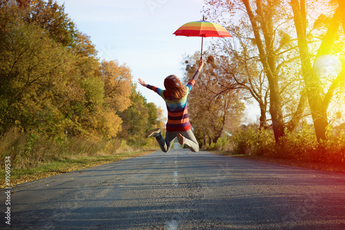 Photo  Picture of jumping lady holding umbrella with arms sideways