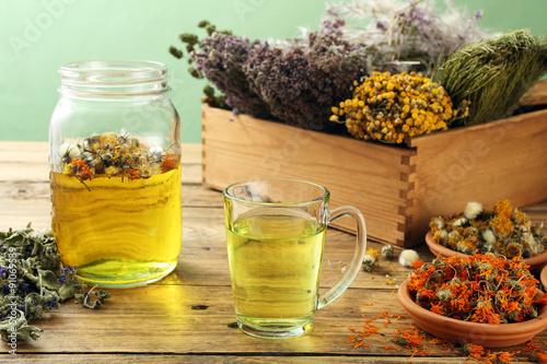 Photo  tisana o infuso di piante spontanee in vaso di vetro sfondo rustico