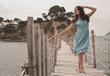 Young happy woman on the bridge near sea