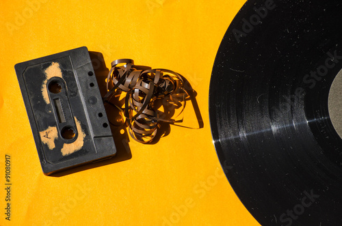 cassette and vinyl record on a colored background orange retro
