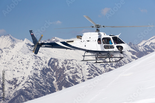 White rescue helicopter in the mountains