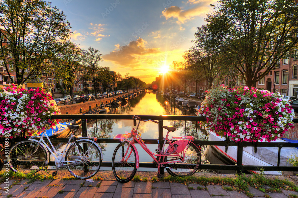 Fototapeta Beautiful sunrise over Amsterdam, The Netherlands, with flowers and bicycles on the bridge in spring