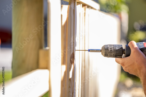 Man erecting a wooden fence outdoors Tableau sur Toile