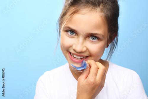 Proste zdrowe zęby dziecka. Dziewczynka z kolorowym aparatem ortodontycznym