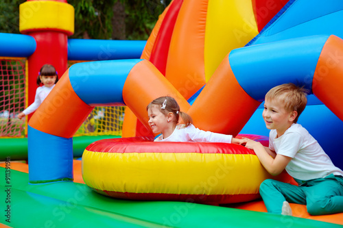 Foto  excited kids having fun on inflatable attraction playground
